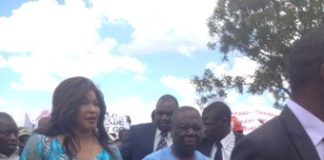 Tsvangirai body shrunk, face pale, feebly pacing while firmly held by his young wife.